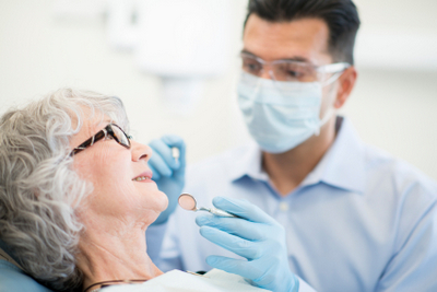 Stock image of dentist checking up a patient in the dental chair